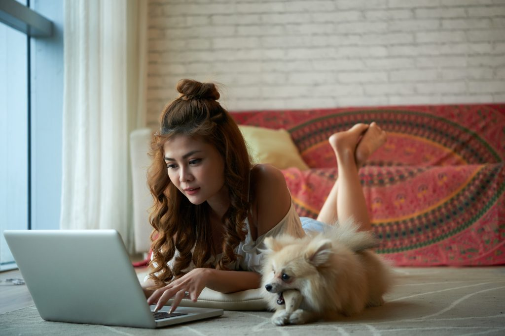 Young woman writes newsletter on her computer next to her dog