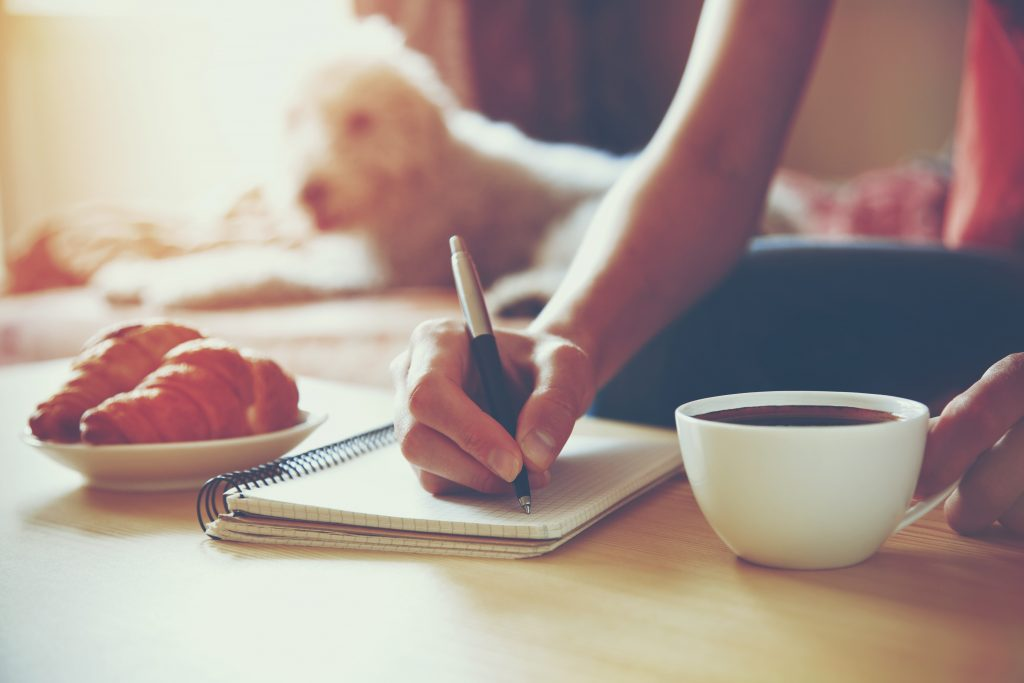 Woman journals for a consistent writing habit with her dog behind her