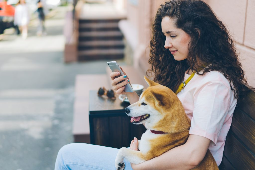 Woman on phone crafting social media copy while hugging her dog