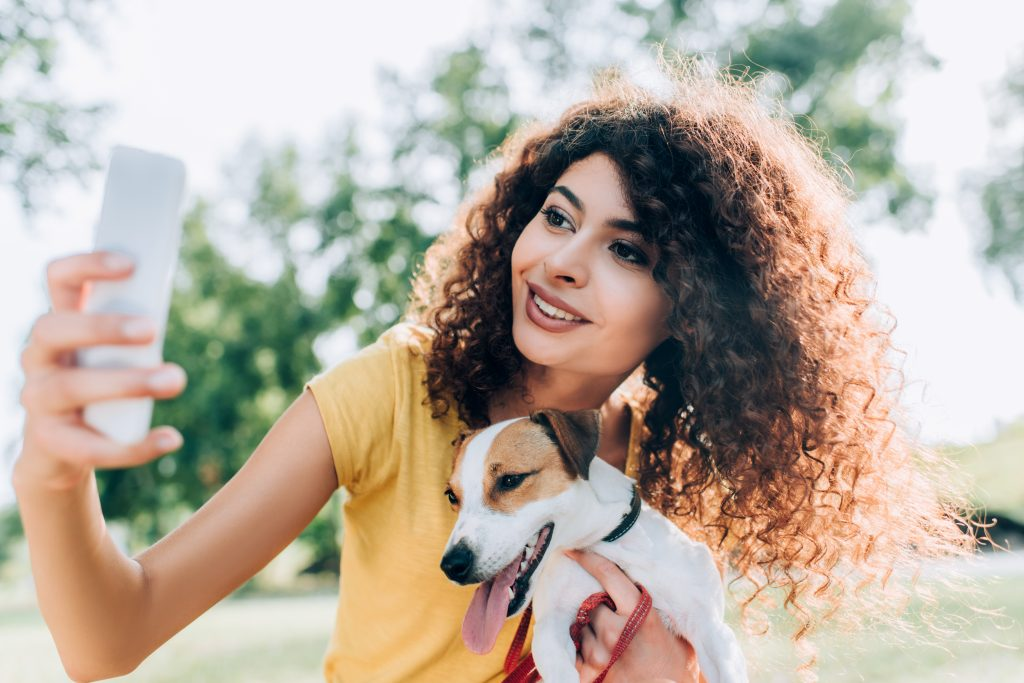 woman taking selfie with dog; blog post on facebook business page